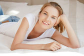 Smiling teenage girl on a bed — Stock Photo