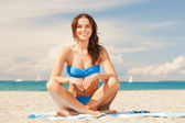 Happy smiling woman sitting on a towel — Stock Photo
