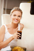 Smiling teenage girl with chips and coke — Stock Photo