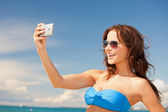 Happy woman with phone on the beach — Stok fotoğraf