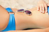Female belly, bikini and shades — Stock Photo
