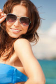 Beautiful woman in sunglasses on a beach — Stock Photo