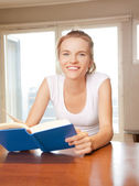 Happy and smiling teenage girl with book — Stock Photo