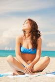 Mulher sorridente feliz sentada sobre uma toalha — Foto Stock