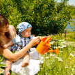 Mother and baby watering camomiles — Stock Photo #11629265