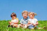 Kids sit on grass — Stock Photo