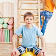 Boy sitting on gymnastic ball — Stock Photo
