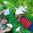 Playing with paper planes on grass — Stock Photo