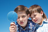 Siblings with magnifying glass — Stock Photo