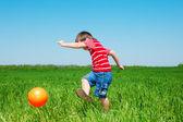 Boy kicking ball — Stock Photo