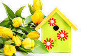 Bird house and yellow flowers — Stock Photo
