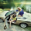 Smiling women in a cabriolet - Stock Photo