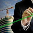 Businessman write a grow up green arrow with construction site background — Stock Photo