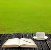 Write on note book and drink hot coffee on garden — Stock Photo