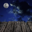 Grunge wooden table with moon in night sky background — Stock Photo