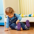 Stock Photo: Baby putting on sandal