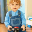 Foto Stock: Portrait of a boy riding a toy car