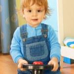 porträtt av en pojke som rider en leksaksbil — Stockfoto
