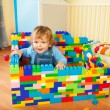 Toddler sitting a castle of toy blocks — Foto Stock