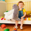 Girl sitting in the baby bed with boys — Stock Photo