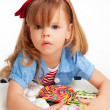Greedy  girl with pile of sweets - Stock Photo
