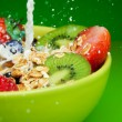 Adding milk to muesli with fruits breakfast — Stock Photo #10959207