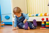 Baby putting on sandal — Stock Photo