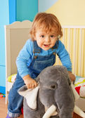 Kid riding a toy elephant — Stock Photo
