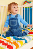 Happy toddler sitting in the baby cot — Stock Photo