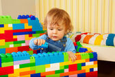 Little boy playing with plastic blocks — Stock Photo