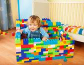 Småbarn sitter ett slott av leksak block — Stockfoto