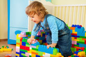 Happy kid claiming out of toy block — Stock Photo