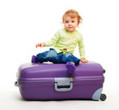 Kid sit on the big suitcase — Stock Photo