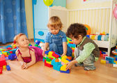 Kids playing with plastic blocks — Stock Photo