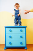 Kid jumping from the cabinet — Stock Photo
