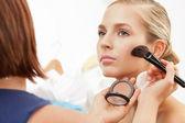 Applying blush on cheeks with blush brush — Stock Photo