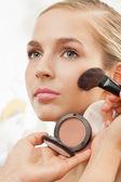 Makeup artist apply blush on cheeks — Stock Photo