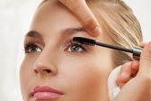 Separating and curling lashes with mascara brush — Stock Photo
