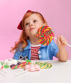 Thoughtful girl with lollipop — Stock Photo