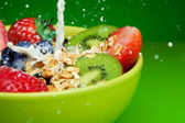 Adding milk to muesli with fruits breakfast — Stock Photo
