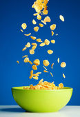 Corn flakes falling to the bowl for breakfast — Stock Photo