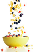 Flying to the bowl corn flakes with berries — Stock Photo