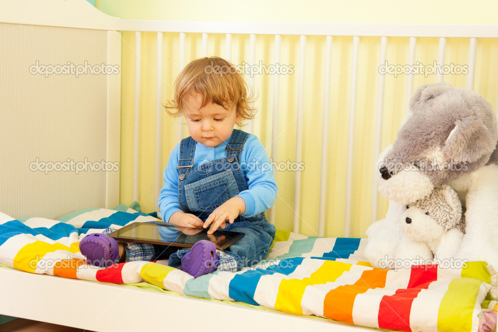 Boy playing with tablet pc sitting in the bed in nursery room — Stock Photo #10957118