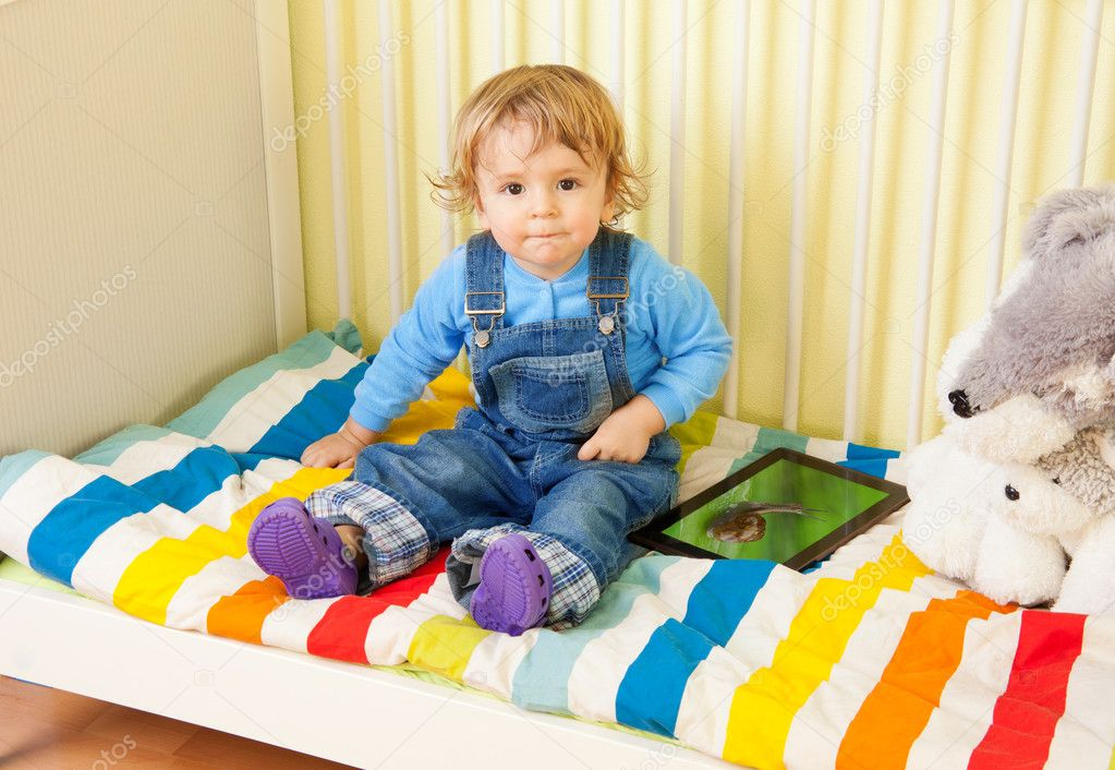 Toddler kid sitting with in the baby bed — Stock Photo #10957121