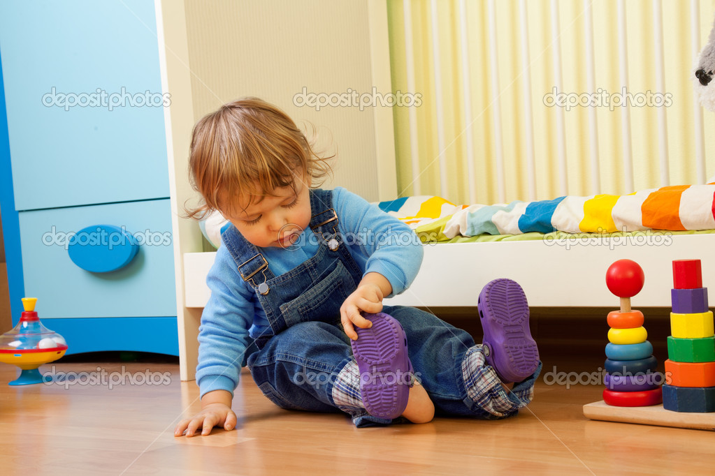 Baby learning putting on sandal sitting in the bedroom — Zdjęcie stockowe #10957133