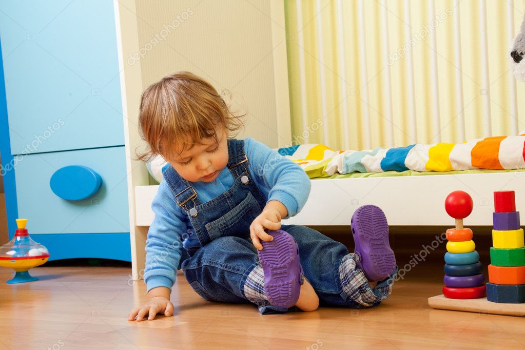 Baby learning putting on sandal sitting in the bedroom — Stock fotografie #10957133