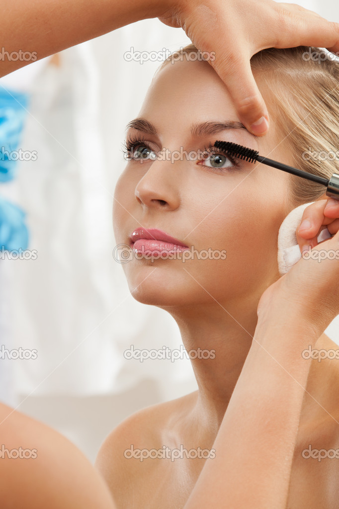 Portrait of a model having separating and curling lashes with mascara brush by makeup artist — Stock Photo #10958720