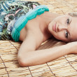 Woman laying on bamboo mat — Stock Photo
