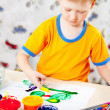 Boy finger paints on paper — Stock Photo