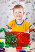 Little boy holding painted picture — Stock Photo